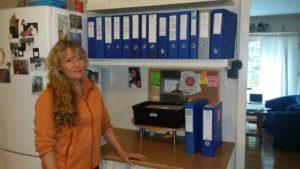 Bilde av Heidi ved siden av ringpermer med saksdokumenter